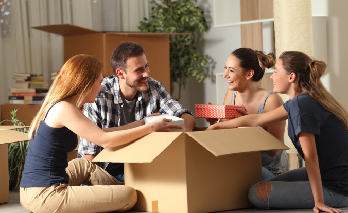 Friends unboxing belongings together after moving into a new house.